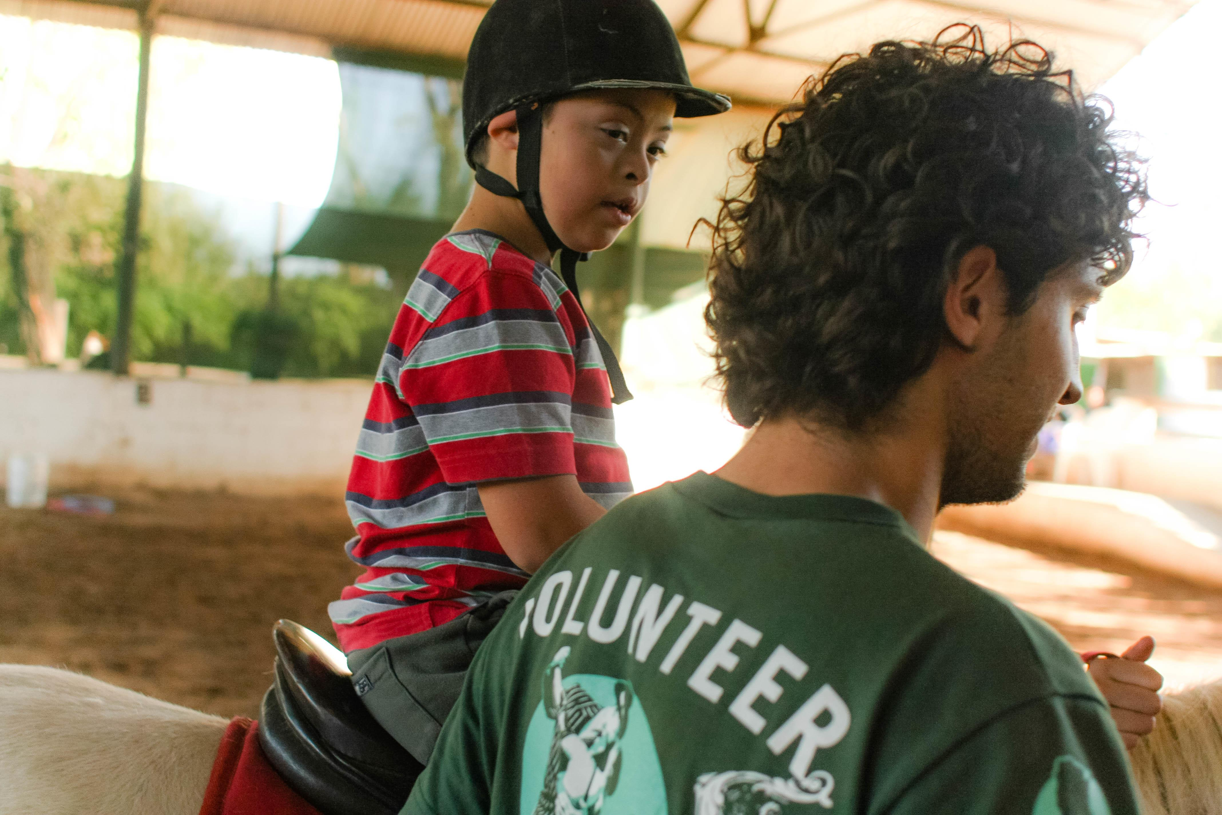 Male Equine Therapy intern working with children in Argentina leads a horse ridden by a child during a therapy session.